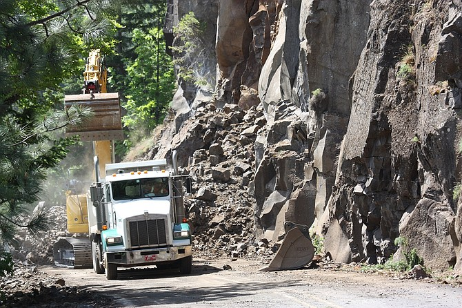 AROCKSLIDE has crews working onsite near Rowena. Above, dump trucks lined up Monday to be loaded with rock that fell onto Highway 30 on May 7. Crews estimate reopening by Memorial Day.