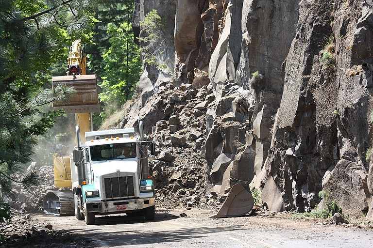A ROCKSLIDE has crews working onsite near Rowena. Above, dump trucks lined up Monday to be loaded with rock that fell onto Highway 30 on May 7. Crews estimate reopening by Memorial Day.