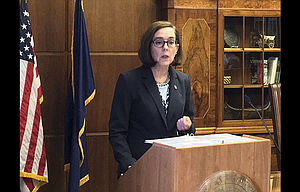 "Oregon Gov. Kate Brown speaks April 27 in the Capitol ceremonial office in Salem. Brown recently signed three executive orders as part of her ""Series of Cost Savings Across State Government"" initiative touted as a broad effort to save money."