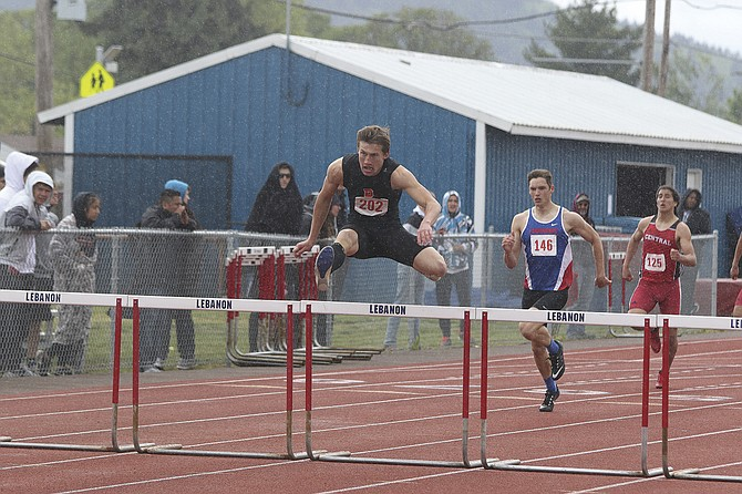 Dallas' Jacob Deming, left, clears a hurdle during the boys 300-meter hurdles race at the Mid-Willamette Conference District Track and Field Championships on Saturday in Lebanon. Deming won the 300 hurdles, long jump and triple jump. The Dragons saw 10 athletes qualify for state during the two-day event.