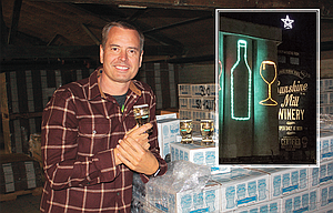 James Martin, founder and CEO of Sunshine Mill Winery, shows off some of the company's products in the winery's warehouse. Inset is a photo of the old grain silos, lit up during the holidays, towering over the east end of The Dalles.