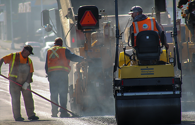 A paving ­­crew works their way down Third Street. Paving work will continue into the roundabout.