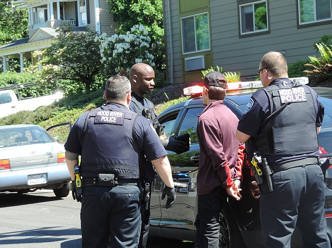 Hood River Police Officer Eme Delancy explains charges to Eric Murphy, 18, a Washington resident, following a vehicle chase and Murphy's arrest Monday on the Heights.