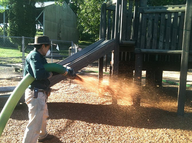 "REXUS crew uses an eight-inch hose Tuesday morning to blow in a layer of ""soft fall"" wood chip material around the Children's Park play structure."