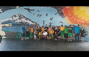 Students from Wahtonka Community School pose in front of a 38-foot-by-13-foot mural they painted in an open-air high school cafeteria in American Samoa.