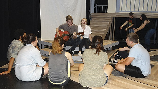 """Gabriel Elmore, with guitar, and Chynna Shurts sing during a rehearsal of """"This Girl,"""" which runs through Saturday."""