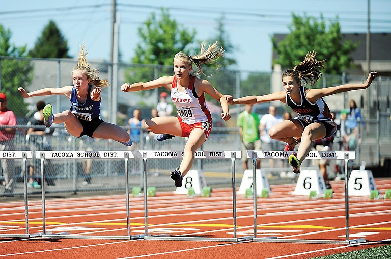 Prosser's Eliza Buttars races to a time of 16.70 in the 2A girls 100-meter hurdles preliminary races Thursday. Flanking her are Brooke Ury of Liberty and Nikola Brzezny of Ephrata.