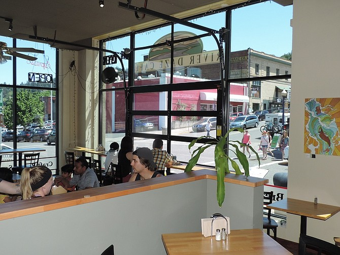 CUSTOMERS enjoy the light from full windows at the renovated River Daze Café. In the foreground is the former da Brewshop space, now integrated with the café.
