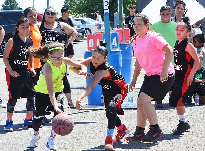Ariana Ramos of Sunnyside's Lady Grizzlies fifth-grade hoops team reaches for the ball as Niya Gutierrez of Grandview's Sour Patch Ballers dribbles past her in Saturday's Hoops for Hope fundraiser for Extra Mile Student Center.