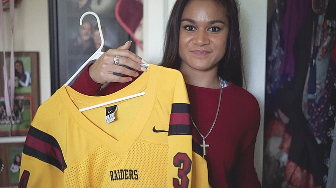 Falute Maitland holds her brother's football jersey. Maitland told her the story about her brother, Seniu Maitland.