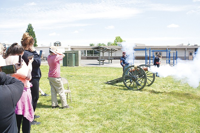 Jack Bentley, by the cannon, and Gale Hemmen, of the Northwest Civil War Council, fire the cannon at LaCreole Middle School in Dallas last week. The demonstration, using blanks, is part of a living history presentation of life and combat during the Civil War.