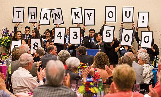 Heritage University graduates hold up the final tally raised Friday at the Bounty of the Valley Scholarship Dinner on the Toppenish campus. The fundraiser matches area scholarships for students attending the four-year school.