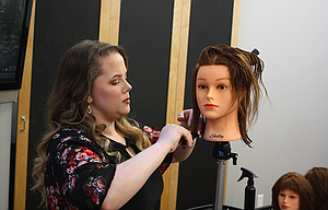 Student Carly Harris practices barbering on a mannequin at the Gorge Academy of Cosmetology. Harris commutes to her classes from Goldendale.
