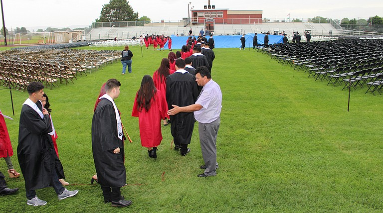 Sunnyside High School Assistant Principal Wally Shearer guides seniors yesterday morning during a rehearsal of tonight's graduation ceremony at Clem Senn Field.