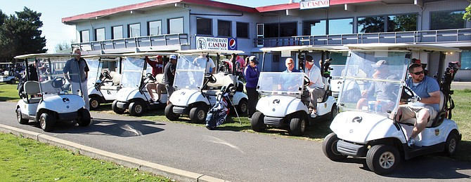 Golf teams depart from the Black Rock Creek clubhouse for the start of the annual Northwest Community Foundation golf tournament.