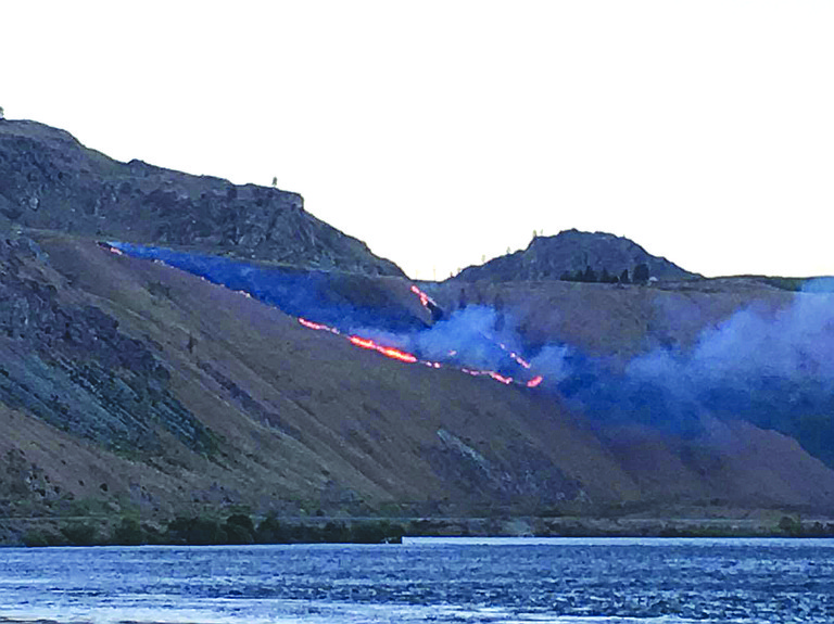 Flames race down a hill near Chelan Monday, June 12.