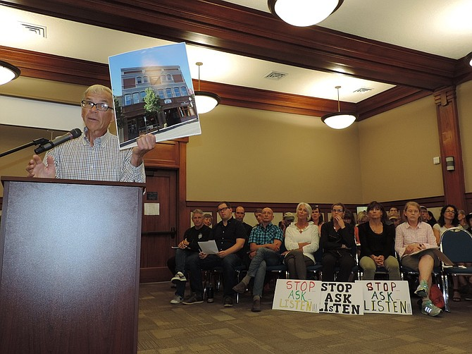 """Plan opponent Jim Reed holds up a photo of downtown's historic Paris Fair, as an example of the kind of place the city should focus efforts for mixed-use housing density. """"It stands as one of Hood River's most cherished landmarks and yet in today's market that kind of mixed use cannot be developed because of Hood River parking ordinance, which calls for a $15,000 in lieu fee per dwelling,"""" Reed noted. He called for a hold on the concept plan """"until they look at giving a tax incentive of 15 years to developers and a mandate that we use mixed use housing."""" Seated with signs, from left, are Bernie Boglioli, Wendy Boglioli, Lisa Sponhauer, and Jennifer Wilson."""