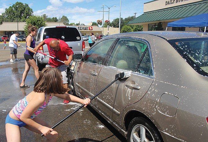 Sunnyside Little Grapplers wrestlers, coaches and volunteers wash cars Saturday to raise money for Nathaniel Wood.