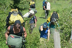 Smokejumpers based in Missoula, West Yellowstone, Mont., Redding, Calif., and Redmond, Calif., came together for refresher training last week in Grangeville. Pictured are moments from June 7. Upon landing, smokejumpers reviewed the jump with instructors, then packed up and hauled their gear up to the nearby road.