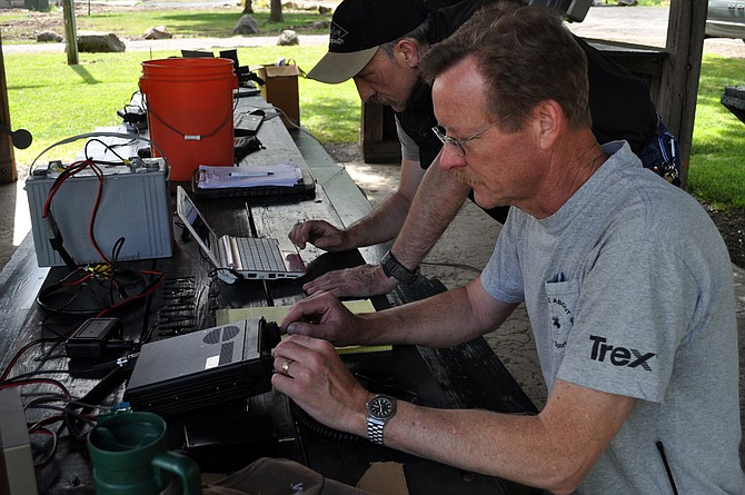 Pictured at a June 2014 event: Dialing in a frequency to make contact with other amateur radio operators at Riverfront Park in Kamiah were (front) Brian Davis of Kooskia and (back) James Cox of Grangeville.