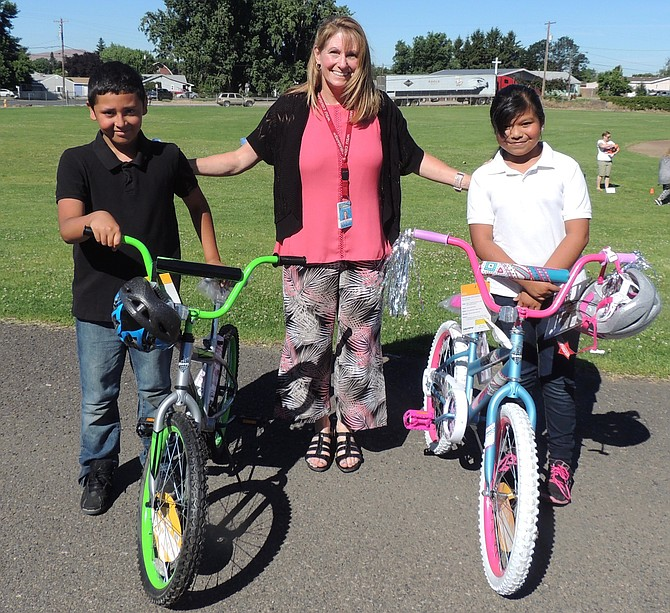 Roosevelt Elementary School Principal Liz Hockens of Granger presents Jose Herrera and Brenda Cortez brand new bikes as their reward for high reading during the recently concluded school year. Both completed fourth-grade. The accelerated reading program is sponsored by the Sunnyside Masonic Lodge. It provided the awards.
