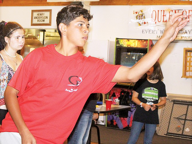 "A dart appears to hover above the hand of Eddy ""Junior"" Almaguer, 14, of Grandview, who won Saturday's youth tournament and is raising funds to compete at nationals."