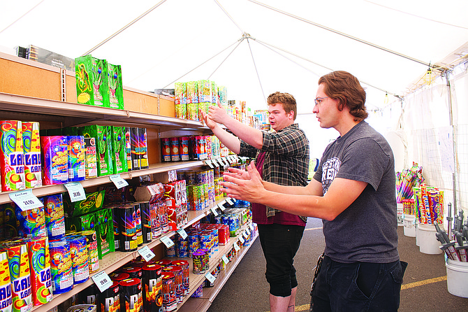 Brad Holtsclaw, left, and Branden Drury, Boomtown Fireworks tent manager, discuss changing the fireworks displays at the stand in Dallas on Tuesday morning. Fireworks retailers around the county are now open for business.