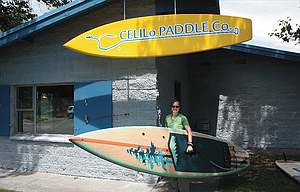 Co-owner Sherry Perry displays one of the paddleboards available for rent at Celilo Paddle Company, a new business located at Riverfront Park in The Dalles.