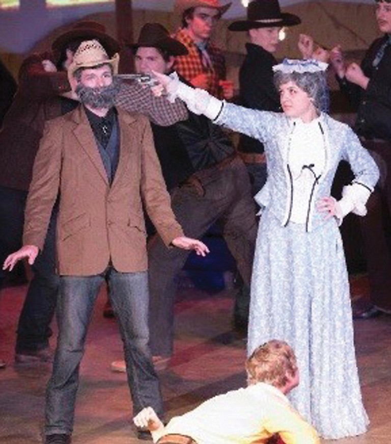 Aunt Eller, played by Reigna Bower, convinces the leader of the farmers to dance at the box social that raises money for a new school.