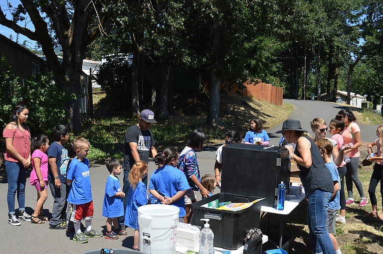 Children stand in line Thursday at Cascade Mobile Manor — next to Les Schwab — for a free, hot meal as volunteers Suzanne Trickey and son Matt, DeeDee Hennessy and sisters Isabella and Bianca Maciel (not pictured, their mother Silvia Maciel) get ready to serve. Meals will run Tuesdays and Thursdays through July 27 at two Hood River locations for anyone ages 1-18.