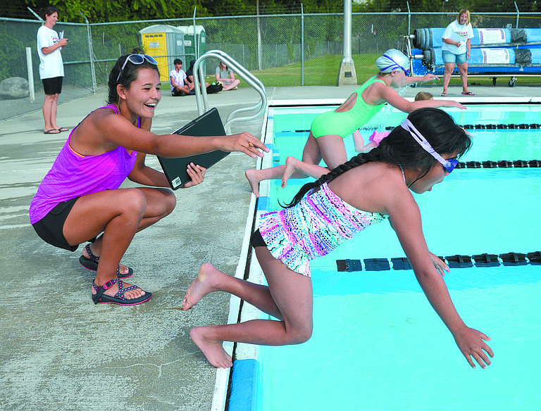 Hanna Smith of Okanogan encourages Angeli Gomez at the start of the age 7-8 girls 25-yard freestyle race on Tuesday.