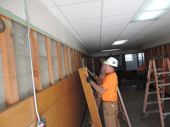 WALLS come gently down: well-preserved hallway wall panels are carefully removed and stored by employees including Dale Lauzon, for reintegration to the Wy'east remodeling project