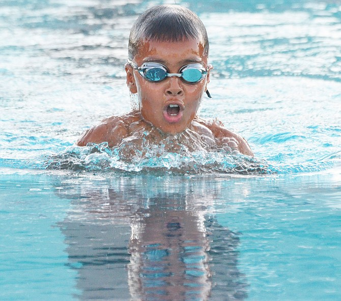Landon Valenzuela races to the finish for the Neptunes in the 8U 40-yard breaststroke.