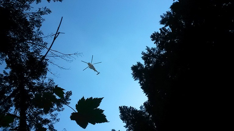 A helicopter delivers water to the Indian Creek Fire.