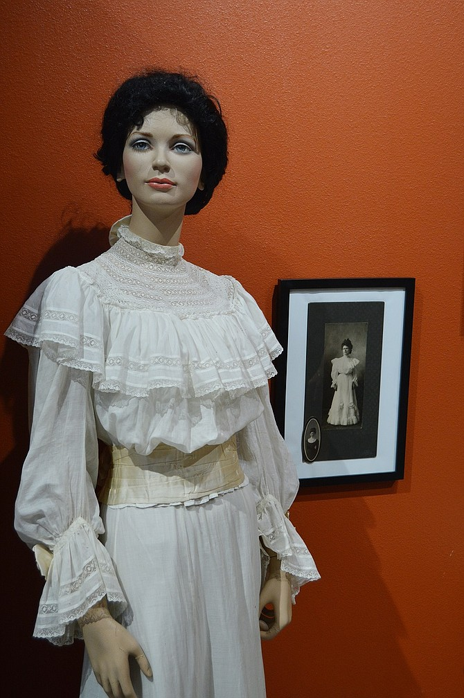The muslin wedding gown worn by Anna Wagner in 1906. The display also includes a photo of Anna wearing her dress and her framed marriage certificate.
