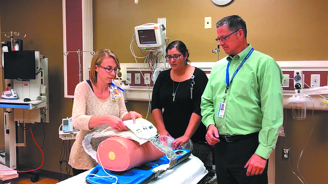 Acute Care Manager/RN Erin Andreas (from left), ER Manager/RN Aliya Quidwai and Zoll representative Chris Baldwin test out the AutoPulse resuscitation device at Mid Valley Hospital.