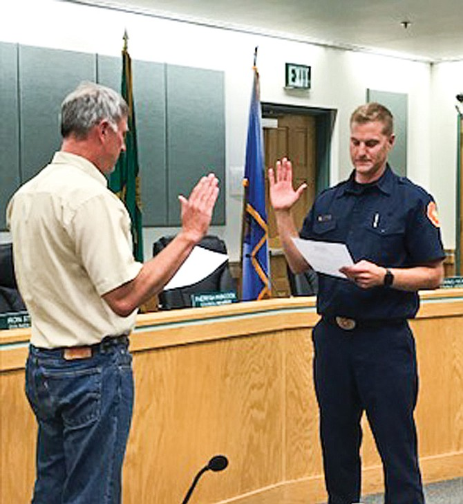 New Sunnyside Fire Department Capt. Chad DenBoer, right, was sworn in during Monday night's City Council meeting by Deputy Mayor Dean Broersma.  DenBoer has been with the department as a professional firefighter for the past several years. His family was on-hand for the pinning ceremony.
