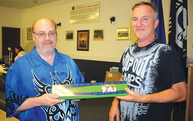 Sandy Sands, left, is presented a handmade cribbage board by James Morrow yesterday.