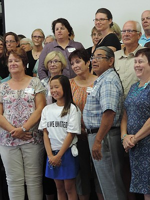"""RECIPIENTS gather to tape part of an upcoming United Way """"Live United"""" video, which stars Hood River's Michelle Graves, 11, center, who helped hand out checks Wednesday."""