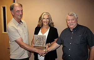 "Ben Mundie (left), reclamationist for the Oregon Department of Geology & Mineral Industries, presents a marble plaque, also pictured below, to landowners Charles and Irene Kornegay, who won the state agency's 2016 ""Good Neighbor Award"" for their efforts to restore the rock quarry they operate."