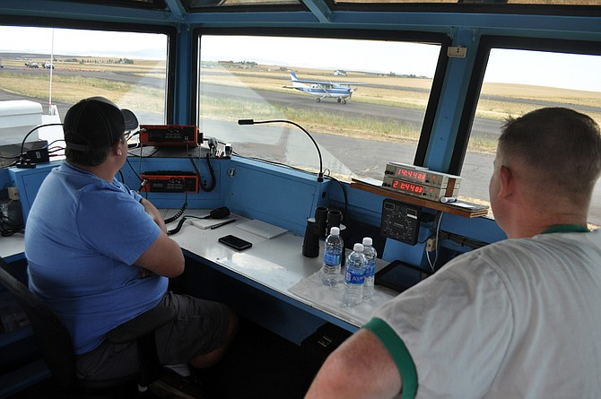 Air traffic controllers (L-R) Michael Wise and Chris Sloan, both of Boise, watch an airplane taxi for takeoff from the FAA temporary tower at the Idaho County Airport last Friday, July 28.
