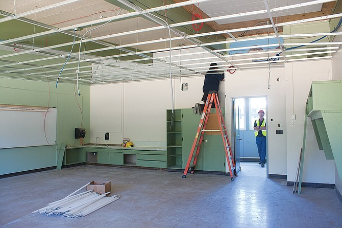 A construction crew member works in a Whitworth Elementary classroom on Monday.