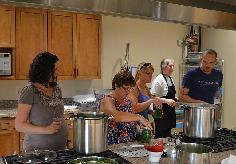 PARTICPANTS in last Thursday's Food Preservation Class load the canner with green beans. From left are Lauren Kraemer, OSU Extension, Vickie Young, Laura Street, Robin Lively and Matt Patterson.