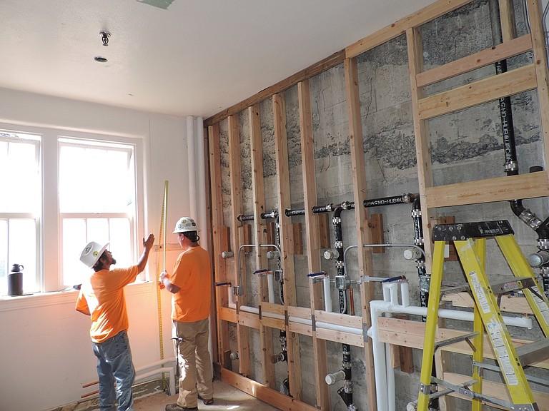 HRMS IN PROGRESS: Steve Salcedo, left, and Jake Meistrell take measurements in the re-opened third floor restrooms.
