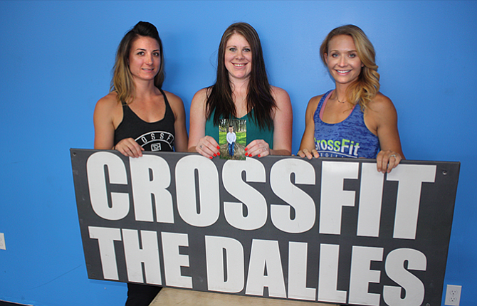 Michelle Austin (center) holds a photo of 4-year-old Parker Lee Perkins, who died in a utility vehicle accident July 30. With Austin are Britt Gannon (left) and Hailey Tenneson, coaches at CrossFit The Dalles. Tenneson and Gannon have organized three days of fundraising activities at the CrossFit gym to support the Perkins family.