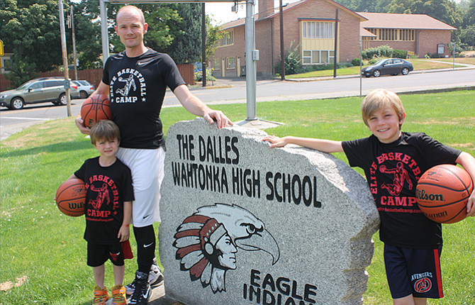Brian Stevens, the new girls' basketball coach at The Dalles High School, is flanked by his two sons, Oliver, 8, and Simon, 5, at TDHS. The boys appear to share their dad's enthusiasm for the sport.
