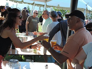 SERVER Kylie Staughton hands over beers at pFriem Family Brewing's fifth anniversary party Aug. 5 at Waterfront Park.