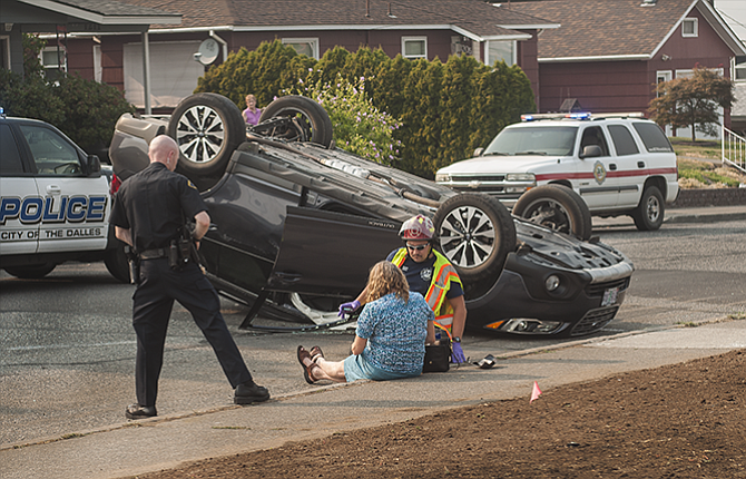 A medic with Mid-Columbia Fire and Rescue sits with the driver of a vehicle that rolled onto its top at 12th and Quinton streets Wednesday evening.