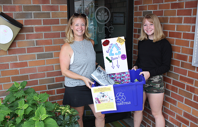 Angela Hanson and her daughter, Emily Johnson — a freshman at The Dalles High School — display some of the donated shoes that have been dropped off at Pure Yoga in The Dalles as part of a program to provide new or lightly used running shoes to local athletes.