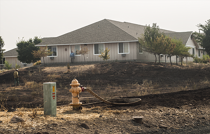 Crews mop up a fire that briefly threatened Canyon Rim Manor in Maupin Thursday afternoon.